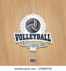 Modern vector volleyball championship logo with olive branch and red ribbon on wooden texture