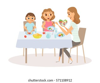 Mom and child eating meal around kitchen table. Happy mother and her two kids sitting eating healthy lunch in home. Smiling woman feeds her daughter and son