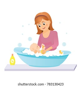 Mom washes the baby in the bath