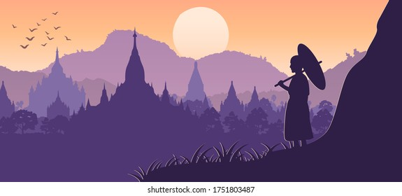 monk hold umbrella on cliff and looks for pagoda sea in Bagan,Myanmar