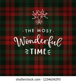 The most wonderful time. Christmas greeting card, invitation with hand drawn mistletoe and white text over tartan checkered plaid. Winter vector calligraphy illustration background.