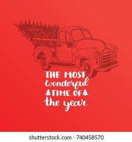 The Most Wonderful Time In The Year lettering on red background. Vector Christmas toy pickup illustration. Happy Holidays greeting card, poster template.