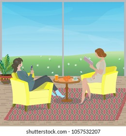 Mother and daughter are  sitting in the armchairs in the living room. Mom reads the book, the girl uses the mobile phone