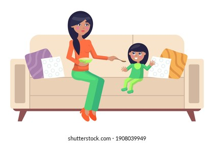 Mother feeding her little daughter sitting on the couch. Woman gives her child porridge from a spoon. Young mom nursing her baby at home. A small girl enjoys the dinner her mother has prepared