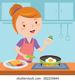 Mother making breakfast. Young woman holding frying pan with a fried egg on a stove.