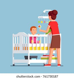 Mother playing rattle to little baby son toddler sitting in crib bed or cot. Woman babysitter looking after newborn boy. Mom and child in kids room. Family childcare. Flat cartoon vector illustration.