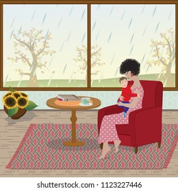 The mother is sitting in the armchair and holding the son in her arms. Rain falls outside