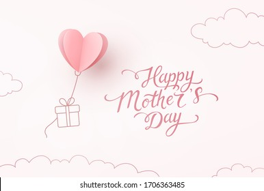 Mother's day greeting card. Vector flying heart balloon with gift box and Happy Mother's Day calligraphy on pink sky background