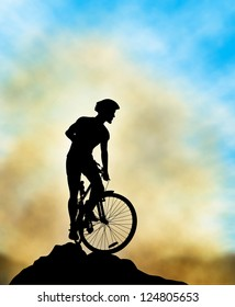 A mountain biker silhouette high on a ridge with background sky and mist made using a gradient mesh