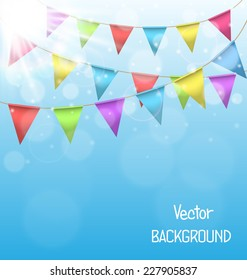 Multicolored bright buntings garlands with glares of the sun on sky background