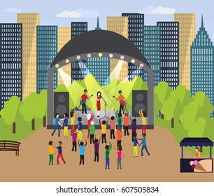Musical festival in the neighborhood park. People dance and have fun outdoor next to scene with singers (band). There are Skyscrapers (blocks) behind event in the park