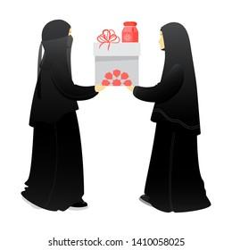 Muslim woman, sisters give a gift to each other. Prophet Mohammad Sunnah to give gifts. Birthday, anniversary, wedding, Ramadan, Eid al-Adha, Eid al-Fitr, Islamic holidays. Hijab, niqab, abaya.1
