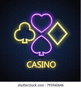 Neon casino sign. Poker, blackjack card suits, spade diamond heart club. Gambling Las Vegas glowing singage banner advertising template design. Gambling game vector illustration brick wall background