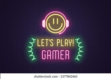 Neon composition of headline Lets Play Gamer. Glowing Neon Emoji with Headphones and text Lets Play Gamer. Bright digital signboard for Gaming industry, Vector. Yellow, pink and green color
