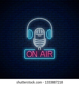 Neon on the air sign with microphone and headphones on dark brick wall background. Glowing signboard of radio station. Sound cafe icon. Music show poster. Vector illustration.