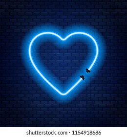 Neon tubes in the shape of a heart isolated on a brick wall background. Sign of love.