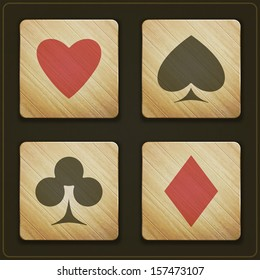 new set of wooden buttons with cards suits symbols on dark background