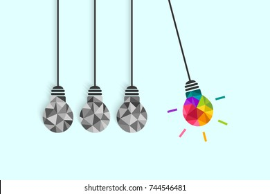 Newton's cradle pendulum with hanging light bulbs as idea and creativity concept. Colorful bulb among plain grey ones.