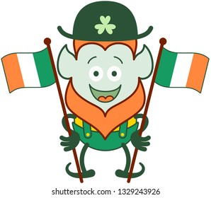Nice Saint Patrick's Day Leprechaun with red beard, pointy ears and traditional hat and costume smiling enthusiastically while holding two beautiful Irish flags