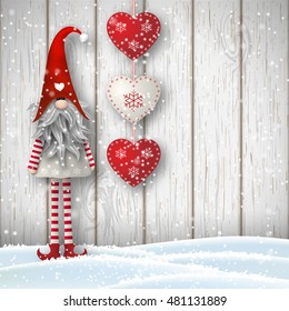 Nisser in Norway and Denmark, Tomtar in Sweden or Tonttu in Finnish, Scandinavian folklore elves, nordic christmas motif, Tomte standing in front of gray wooden wall in snow, with red decorated hearts.