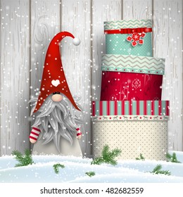 Nisser in Norway and Denmark, Tomtar in Sweden or Tonttu in Finnish, Scandinavian folklore elves, nordic christmas motive, Tomte standing in front of white wooden wall in snow, with stack of colorful