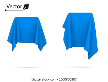 Object covered with blue silk cloth. Box, cube. Surprise, award, prize, presentation concept. Reveal a hidden object.