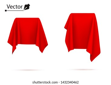 Object covered with red silk cloth. Box, cube. Surprise, award, prize, presentation concept. Reveal a hidden object.