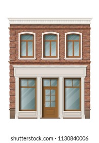 Old brick building facade with windows and shop on ground floor. Traditional classic architecture of front building. Storefront with large windows on the ground floor.