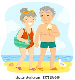 Older couple in swimsuits walking happily on the beach
