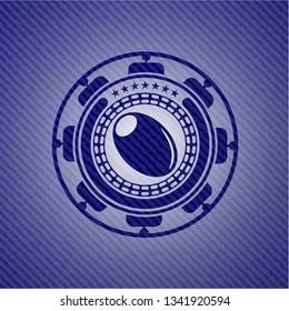 olive icon inside badge with denim background