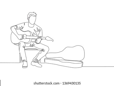 One continuous line drawing of young happy male guitarist sitting and busking by playing guitar on the uptown road. Street musician artist performance concept single line draw design illustration