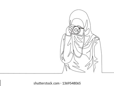 One continuous line drawing of young pretty muslimah with headscarf holding dslr camera on her hand. Beauty Asian woman model in trendy hijab fashion concept single line draw design illustration