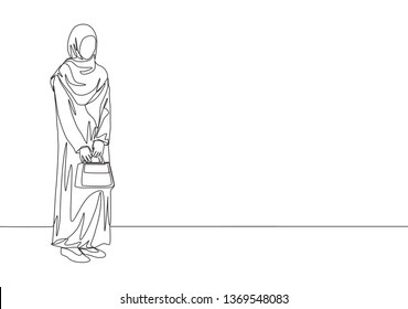 One continuous line drawing of young attractive muslimah with traditional Arab cloth holding little bag. Beauty Asian woman model in trendy hijab fashion concept single line draw design illustration