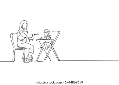 One continuous line drawing of young Islamic mom feeding her toddler health food on baby dining table. Happy Arabian muslim parenting family concept. Dynamic singleline draw design vector illustration