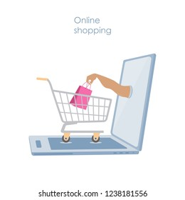 Online shopping or e-commerce concept.  Opened  laptop with a shopping cart and a hand holding a bright shopping bag