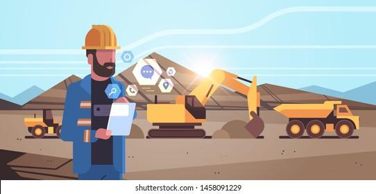 open pit man worker in helmet using mobile app excavator loading soil on dump truck professional equipment working on coal mine production opencast stone quarry background portrait horizontal