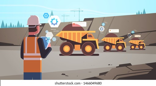 open pit man worker in helmet using mobile app. controlling dumper trucks. professional equipment, working on coal mine production. opencast stone quarry background portrait horizontal.