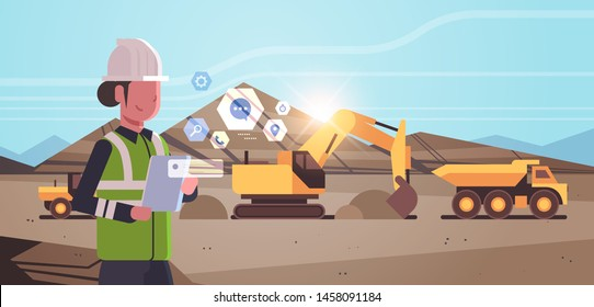 open pit woman worker in helmet using mobile app excavator loading soil on dump truck professional equipment working on coal mine production opencast stone quarry background portrait horizontal