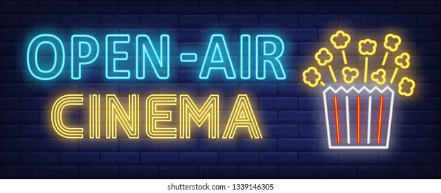 Open-air cinema neon text with popcorn paper box. Entertainment concept, advertisement design. Night bright neon sign, colorful billboard, light banner. Vector illustration in neon style.
