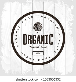 Organic natural and healthy farm fresh food retro emblem. Monstera leaf vintage logo isolated on white wood board background. Premium quality loft grunge threadbare wood texture illustration mock up.