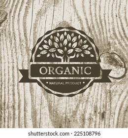 Organic product badge with tree on wooden texture. Vector illustration background.