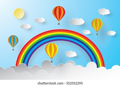 Origami hot air balloon and rainbow with blue sky .paper art style.