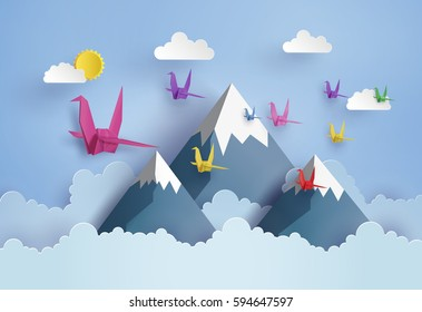 origami made colorful paper bird flying on blue sky over moutian with cloud . paper art and craft style.