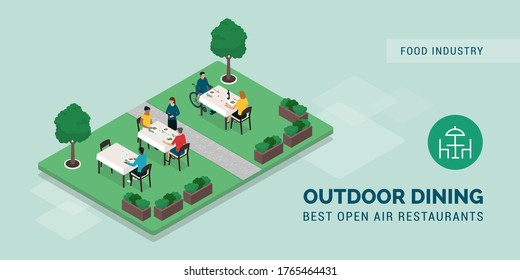 Outdoor dining restaurant: people eating outside in a beautiful garden and waitress taking orders