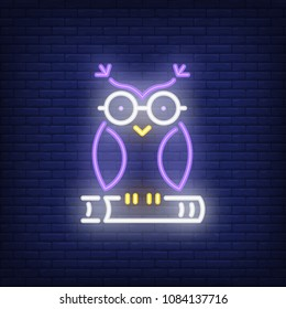Owl on book neon sign. Clever owl in glasses sitting on book. Night bright advertisement. Vector illustration in neon style for education and literacy