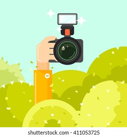 Paparazzi hand holds photo camera, vector illustration. Spy hides in green bushes with photo camera. Journalist sit in ambush and make sensational shot. Paparazzi concept in flat style