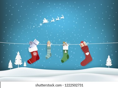 Paper art illustration of Santa and stockings and gift box hanging on a clothesline. Christmas holiday season background
