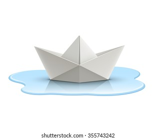Paper boat in puddle