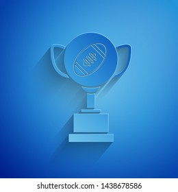 Paper cut Award cup and American football ball icon isolated on blue background. Winner trophy symbol. Championship or competition trophy. Paper art style. Vector Illustration