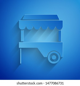 Paper cut Fast street food cart with awning icon isolated on blue background. Urban kiosk. Paper art style. Vector Illustration